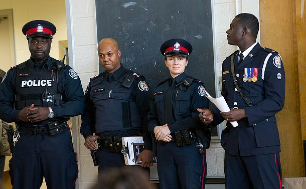 Four officers in uniform, one in dress uniform looking into the camera.
