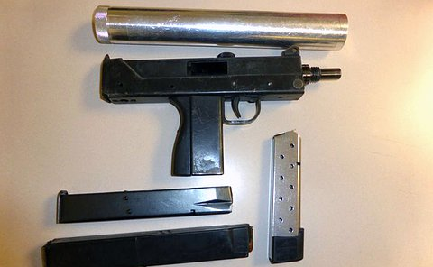 A black firearm and magazines with a round silver cylinder