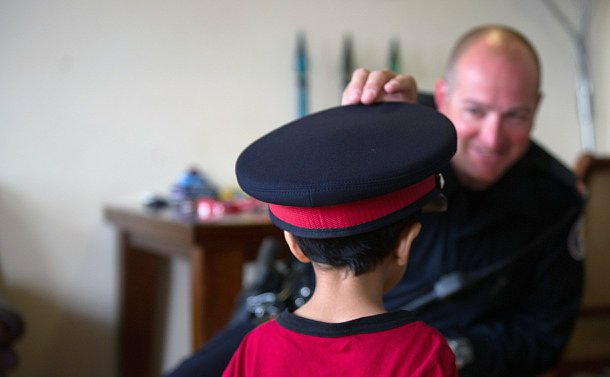 A man in the background, facing camera but out of focus, plays a police hat on a boy in the foreground whose back is to the camera, but he is focus.