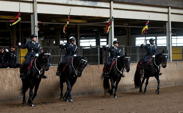 Four members on horses with lances raised