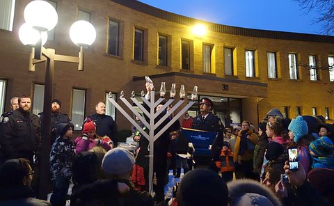 A six-foot tall menorah with people, some in TPS uniform gathered around