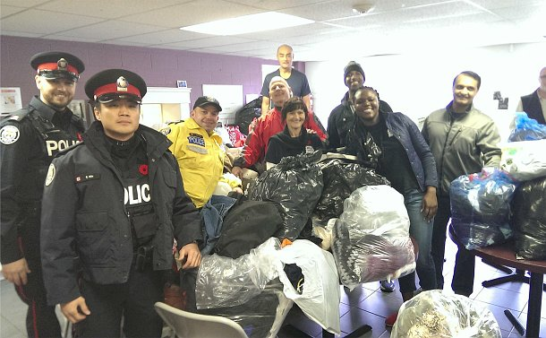 A group of men in TPS uniform and other men and women with bags around them