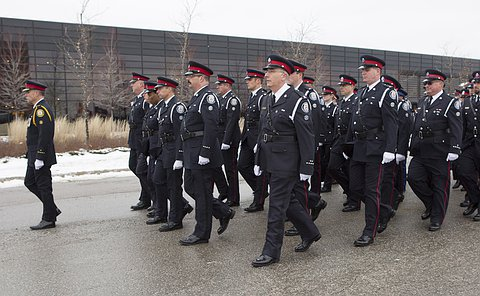 One man in Toronto police uniform walks in front of a larger group of men and women in Toronto Police uniform