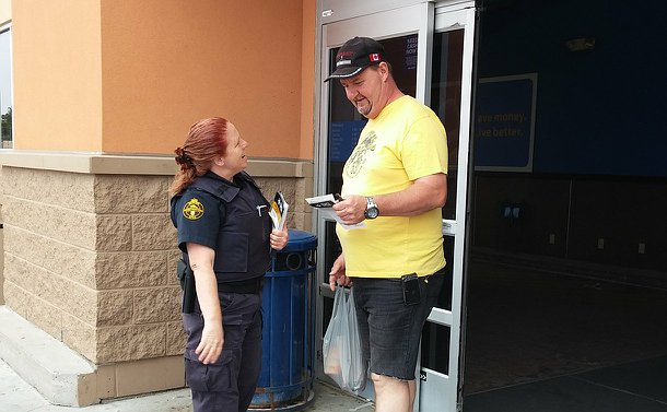 A woman in OSPCA uniform talks with a man holding a piece of paper