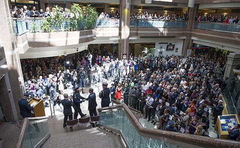 Four men stand on a staircase in front of a crowd of hundreds in a building lobby