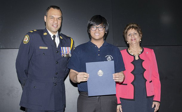 A man in TPS uniform and a woman standing with a teenage boy holder a certificate folder