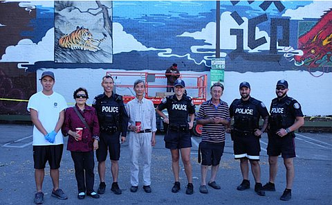 A group of people, including men and women in TPS uniform in a parking lot with a mural on a wall behind them