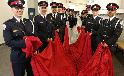 Men and women in TPS uniform in two rows holding large Canadian flag