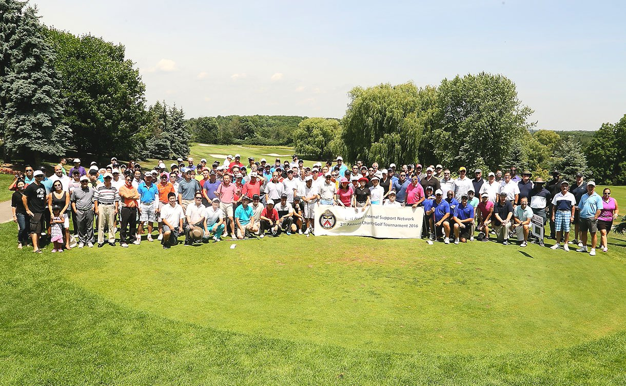 A large group of people standing in the middle of a golf field.