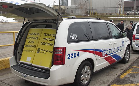 Several men and women in TPS uniform near a TPS minivan with it's trunk open displaying food drive boxes