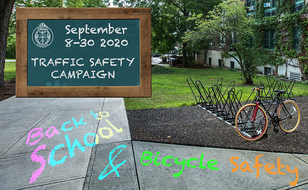 """A bicycle on a rack with chalk on sidewalk """"back to school"""" and """"bicycle safety"""""""