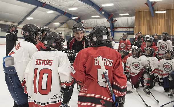 A man leans over to speak to kids in hockey uniform