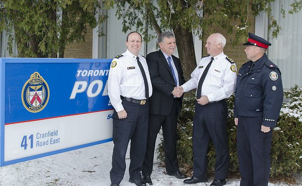 Four men in Toronto Police  uniform beside the 54 Division sign. The two men in the middle are shaking hands and facing each other, the other two are looking at the camera.