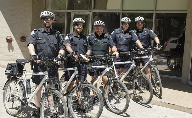 Six men in TPS uniform holding police bikes in a row