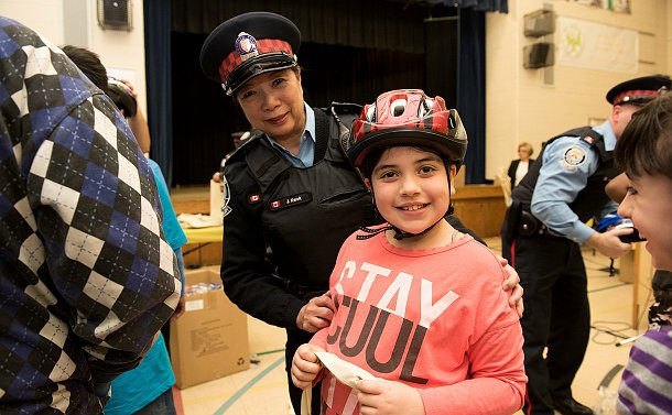 a woman in auxiliary uniform smiling with a young girl who is wearing a helmet