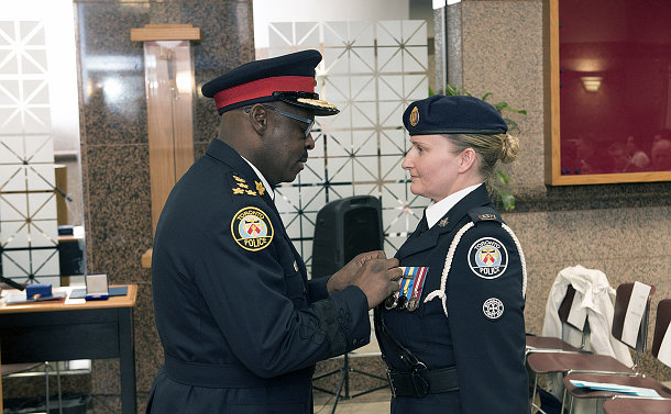 Man and a woman in police uniform; man is pinning a medal onto woman's chest