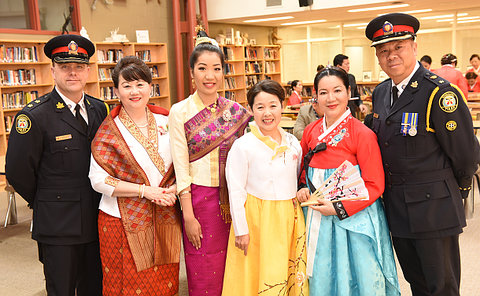 Two men in TPS uniform with women in cultural dress