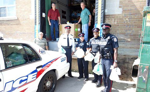 Three male and one female officers with three other men standing beside a TPS car at a loading dock