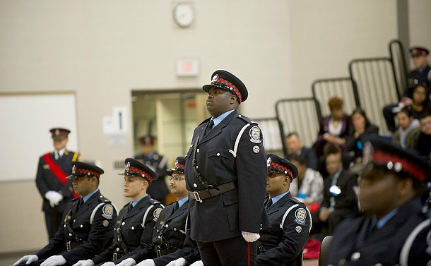 A man in TPS auxiliary uniform stands among a group of people seated in TPS Auxiliary uniform