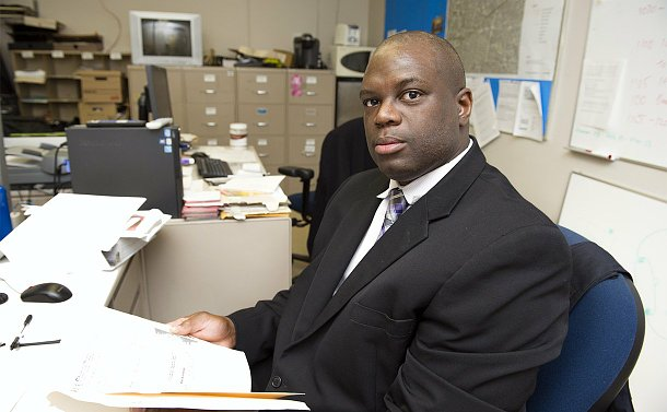 A man sitting at a desk holding a file folder