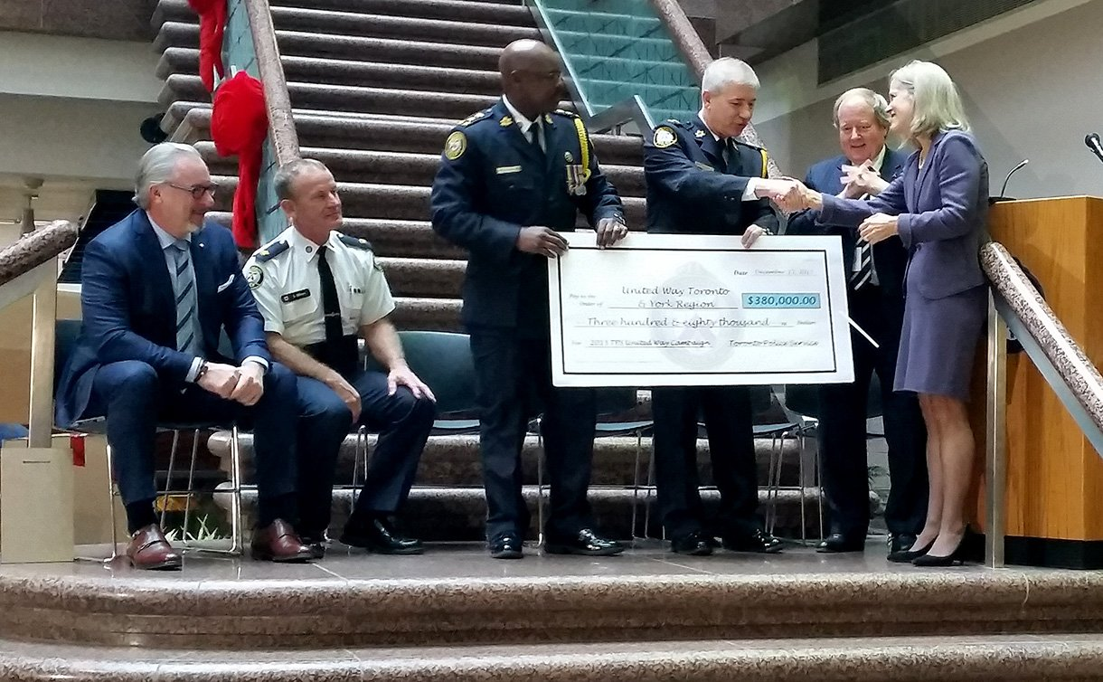 Two men in uniform handing a large cheque to a woman