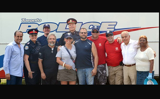 A group of people with a man and woman in TPS uniform against a police command vehicle