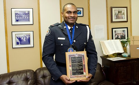 A man in TPS uniform holding an award