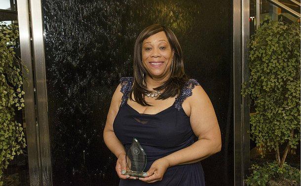 A woman holds an award