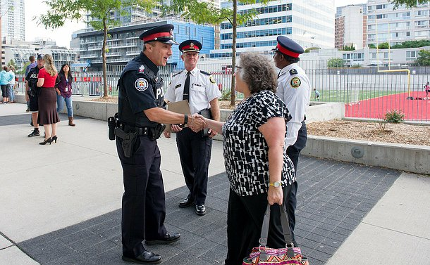 A man in TPS uniform shakes the hand of a woman alongside fellow officers in TPS uniform