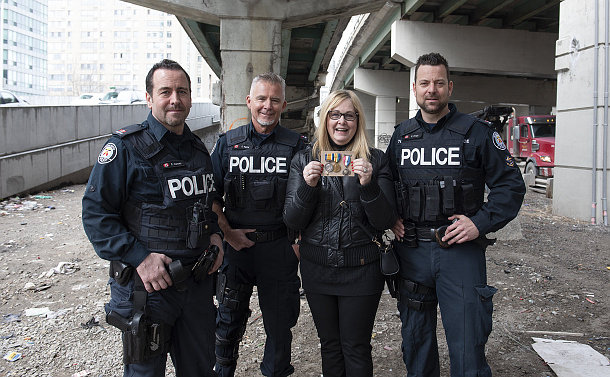 Three men in TPS uniform with a woman holding medals under a highway overpass