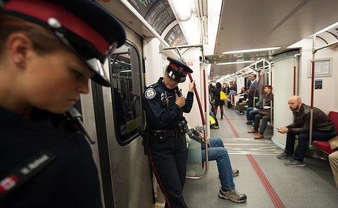 A female officer inside a subway train bending down to listen to her radio