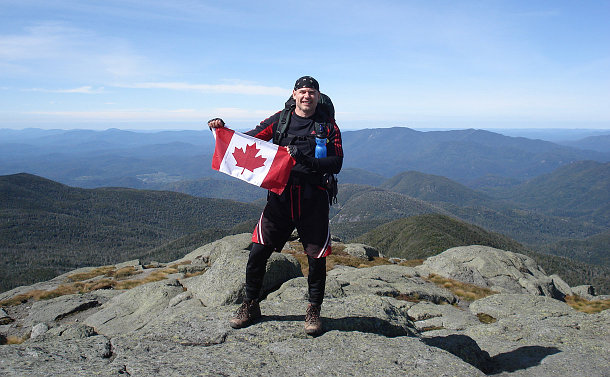 A man on a mountain with a Canadian flag