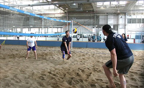 A man hits a volleyball into the air on a beach volleyball court