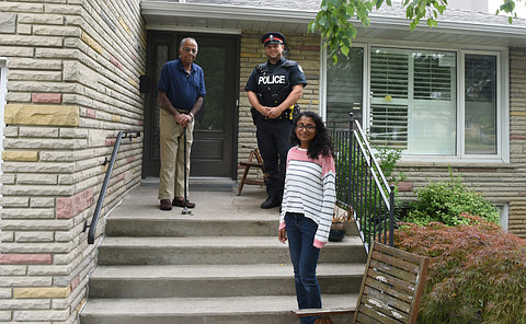 An elderly man with a cane, man in a police uniform, and a young woman, standing on the stairs in front of a house entrance
