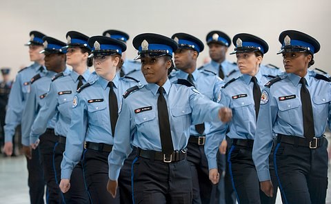 Women and men in uniform, arms swung in the air as they look to their right and march in a queue.
