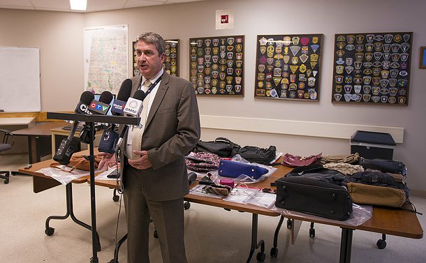 A man speaks at a group of microphones while standing in front of a table of goods, mostly backpacks and handbags in view