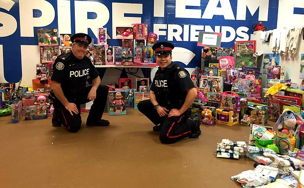 Two officers squatting next to boxes full of toys