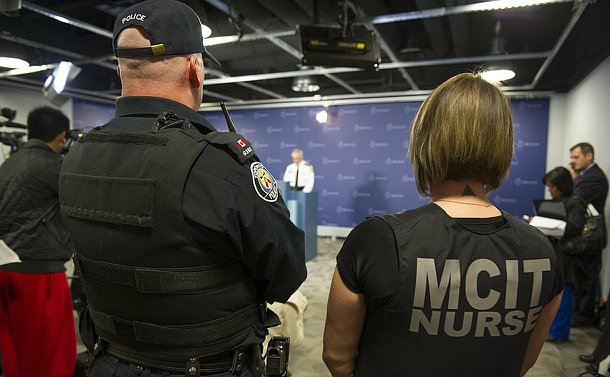 View from behind of a man in TPS uniform and a woman wearing a vest with the words MCIT Nurse on her back watching a man speak at a podium