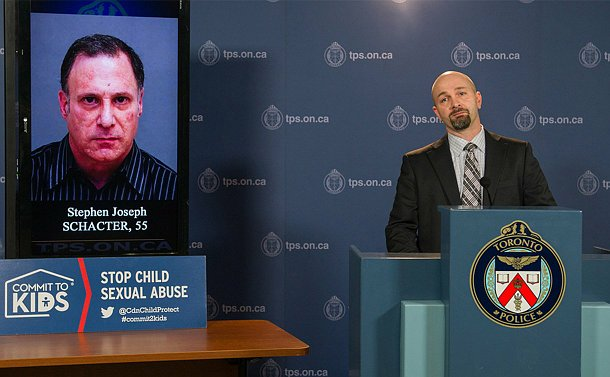 A man stands a a podium beside a TV with the photo of another man