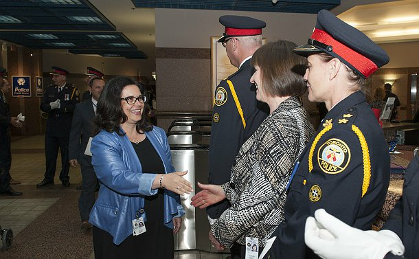A woman shakes hands with another woman in a line of TPS officers