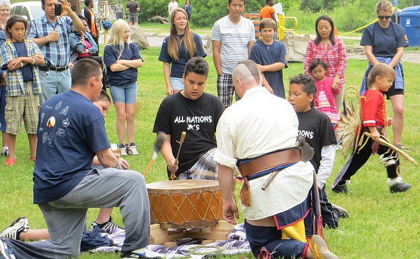 A group of people drum a large traditional leather drum