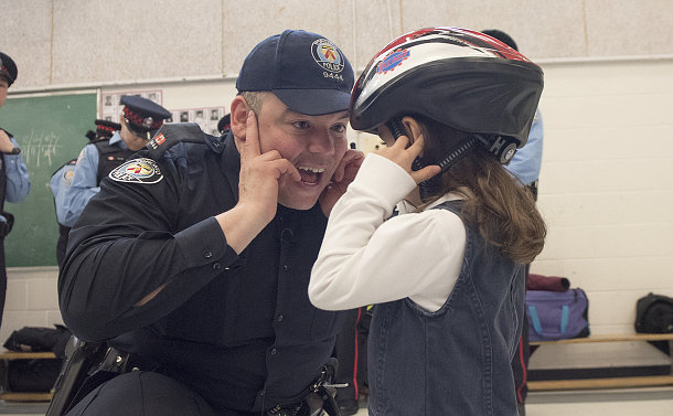 A girl in a bicycle helmet with a man in TPS uniform crouched down