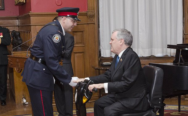 A man in TPS uniform shakes hands with another seated man
