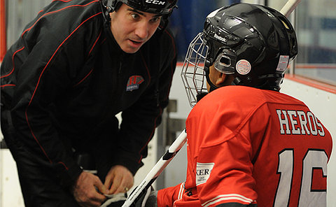 A man tightens the laces of a child in hockey equipment