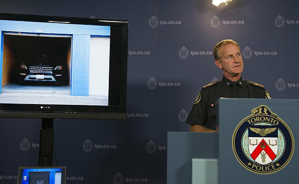 A man in TPS uniform speaks at a podium beside a television with a photo of vehicle in a garage on it