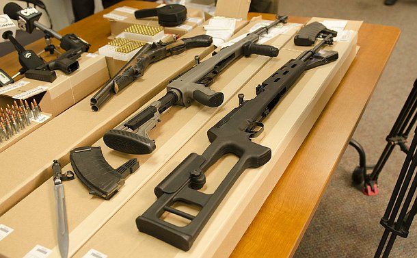 A table with rifles, a sawed-off shotgun, a handgun and rounds of bullets