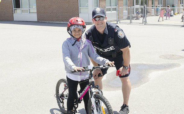 A man in TPS uniform crouches beside a girl on a bike in a school playground