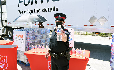 Man in a police uniform holding a bottle of water in front of him.