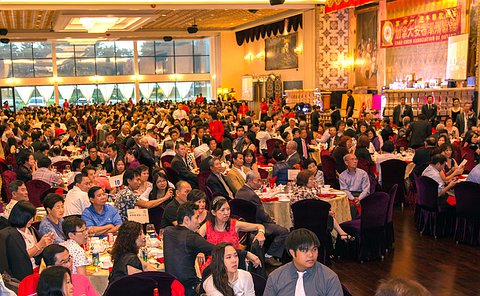 A large group of people seated at tables in a banquet hall
