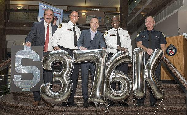 Five men, three in TPS uniform in front of 3-7-6-K balloons